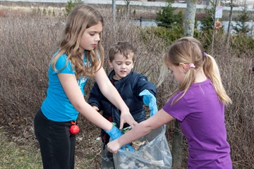 Charlotte Schankula, 8, Connor Pacheco, 4, and Evelyn Pacheco, 8 clean up the park  on Iron Block Drive as their participation in Earth Day. Several bags of garbage were collected.