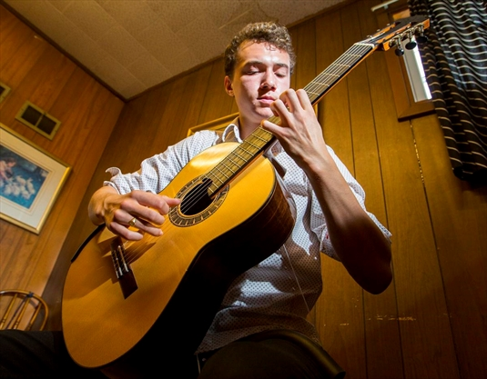 Evan Dim plays his guitar on a world stage