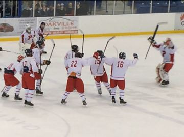 Members of the L.B. Pearson Patriots boys hockey team celebrate after officials decided a shot by Mason Sheppard entered the net moments earlier.