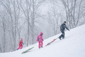 In this file photo, children are hauling their sleds up the hill at Garth and Stone Church Resevior during a snow storm. Environment Canada is calling for 10 to 15 centimetres of snow this weekend. Plenty to make city-approved toboggan hills lots of fun.