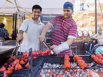 Shaq Emhed, left, and Anwar Khan cook up some chicken during the Gerrard India Bazaar's 13th annual Festival of South Asia on Sunday evening. The two day festival took place along Gerrard Street East and featured dozens of food vendors as well as live performances.