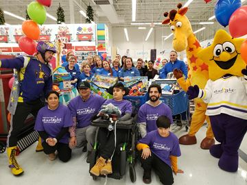 The family of Zain Khalid, 11, centre, surrounds him with store staff and Captain Starlight along with mascots after the family completed the 3-minute Starlight Children's Foundation Canada dash program on Wednesday morning at the Whitby Toys 'R' Us. The family filled five shopping carts full of toys which Zain gets to keep.