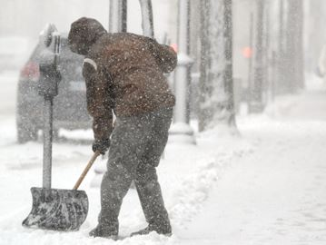 Paul Russell shovels the sidewalk outside Looney Tunes on Brant Street in Burlington Wednesday.