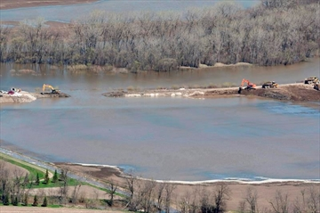 The breach in the dike at the hoop and holler bend is seen along the Assiniboine River outside of Portage La Prairie, Man, Saturday, May 14, 2011. A settlement approval hearing is scheduled for a $90-million settlement stemming from a class action lawsuit launched by Lake St. Martin, Pinaymootang (Fairford), Little Saskatchewan and Dauphin River First Nations against the federal and provincial governments over 2011 flooding. THE CANADIAN PRESS/Jonathan Hayward