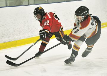 Ryan Bath of the Midland Bourgeois Motors atom Centennials checks an Innisfil Winterhawks opponent during regional Silver Stick action Dec. 6 in Midland. Midland won the game 4-2.