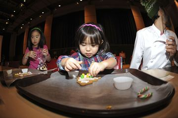 Nanami Kita decorates her gingerbread cookie at the Winter Family Festival Sunday at the Japanese Canadian Cultural Centre.
