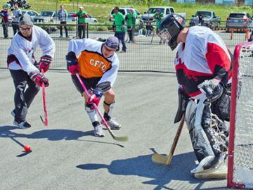 Richard Puddy (from left) and Sgt. Sylvain Martel tussle with goalie Darryl Delong during a game Saturday at the Collier memorial ball hockey tournament to honour Sapper Brian Collier who died in Afghanistan.