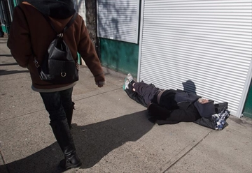 A woman walks past a man sleeping on the street in the Downtown Eastside of Vancouver, B.C., on Tuesday, February 21, 2017. Cities struggling to house their homeless are asking the federal Liberals to rethink the government's cornerstone homelessness program amid concerns about burdensome reporting requirements and inadequate funding models.THE CANADIAN PRESS/Darryl Dyck