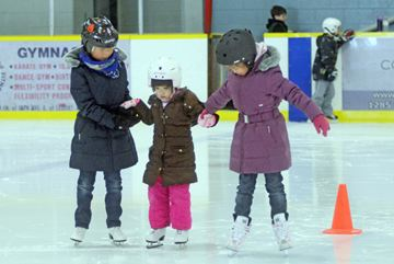 It's the first time on skates for Sherry Li. She's getting a skating lesson from sister Sandra (right) and friend Joanna Wang.