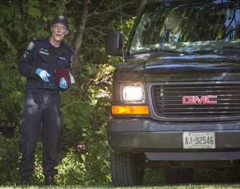 A member of the Toronto Police Service chats with a man in an unmarked vehicle on a property along Mallory Cres. in Toronto during an investigation relating to Bruce McArthur on Wednesday, July 4, 2018. Toronto police say they will be providing an update today in the case against alleged serial killer McArthur. THE CANADIAN PRESS/ Tijana Martin