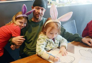 Karlee Crittenden, 5, paints an Easter egg as Mackenzie, 9, hugs her dad Dion Crittenden.