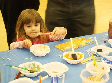 Kayla Zaldin, 3, works on her mini menorah at the Chanukah carnival today at Thornhill's Shaar Shalom Synagogue.