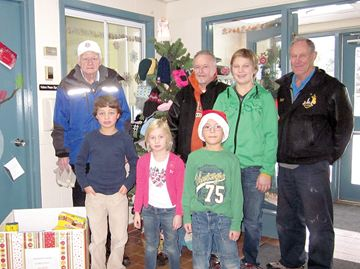 The families at Alliston Community Christian School recently collected non-perishable food items, hats and mittens for the Alliston Lions Club Christmas hampers. Pictured in front of the school's hat and mitten tree are several students with representatives from the Lions Club.