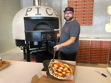 Pi Co. owner/franchisee Kevin Lanthier pulls out a 'Margherita' from the oven.
