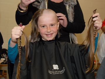 Bryn Coutts holds up the hair she is donating before getting buzzed bald at the Shave for the Brave fundraiser at W.H. Day Public School Friday, April 4.