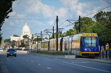 With the Minnesota State Capitol in St. Paul on the horizon, the Green Line runs in the center of University Avenue towards Minneapolis.