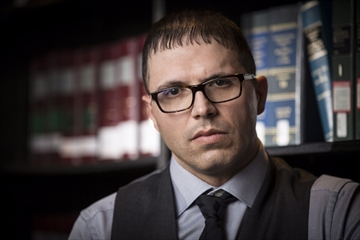 Lawyer Adam Savaglio poses in the offices of Scarfone Hawkins LLP, Dec. 7. Savaglio is representing a woman (who doesn't want to be identified) who filed a human rights complaint after being sexually assaulted.