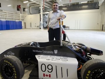Ali Emadi, director of MacAUTO, shows off a hybrid car built by students at one of the McMaster Automotive Resource Centre garages.