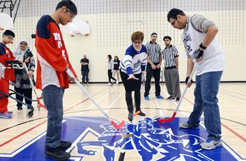 Milliken Mills High School principal Catherine McGinley drops the ceremonial puck with MM Knight Joey Sakha (left) and Middlefield CI's Sunny Patel.