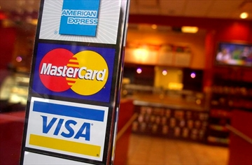 Signs for American Express, MasterCard and Visa credit cards are shown at the entrance to a New York coffee shop on April 22, 2005. The federal government will announce today that major credit card companies have agreed to lower the fees they charge the country's businesses, The Canadian Press has learned. A senior government source with knowledge of the announcement says Ottawa has reached voluntary, five-year deals with Visa, Mastercard and American Express that the feds expect will help small and medium-sized companies save a total of $250 million per year. THE CANADIAN PRESS/AP, Mark Lennihan
