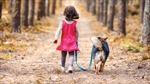 Little girl walks with a dog