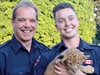 Firefighters and a lion cub