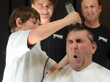 Eric Jolliffe, York Region Chief of Police, has his head shaved by cancer survivor Allesandro Cicciarella during the Cops for Cancer fundraising event at Vaughan Mills Mall in Vaughan, Saturday.