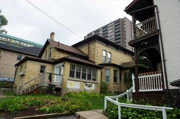 The properties between 242 and 262 Queen St. S., including Oneroof Youth Services, are under negotiation to be bought and redeveloped into an eight-storey rental apartment near downtown Kitchener.