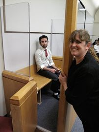 Tanenbaum CHAT Kimel Centre student Max Levy, portraying the accused, sits in the Newmarket courthouse prisoners dock while teacher Lynne Howard looks on.