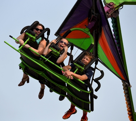 The Luck family, mom Mandy, left, and kids Samantha and Sean, enjoy a spin on one of the midway rides.