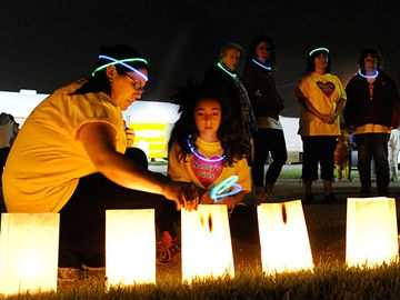 Here, Meaghan Homewood ,left, helps her sister Ella ,9, light luminaries for their Aunt Nancy Robar.