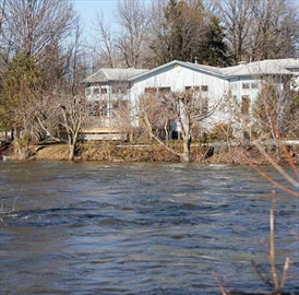 A home along the Jock River at Greenbank Road looks onto fast-moving water on April 12. The river - which is quite shallow in the summer - is running fast due to the quick thaw and recent rains.