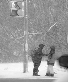 A mother brushes snow off her daughter's jacket while waiting for the traffic light to change for them to cross
