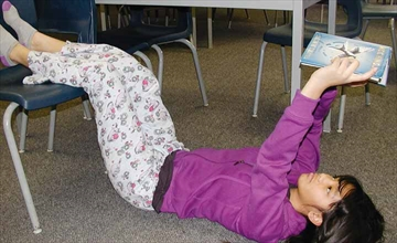 Sacred Heart Catholic High School grade seven student Alyanna Tabilin is lying down and wearing pj's as she reads her book in the fundraising read-a-thon involving grade seven and eight students which was held at the school in Stittsville last Friday, Feb. 28. See page 2.