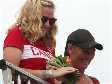 Mark Oldershaw's girl friend Annamay Pierse catches his bouquet  after winning the bronze in the 1000 metre canoe event  at the London 2012 Olympic Games at the Eton Dorney  in London.  August 8, 2012