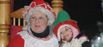 Mrs. Claus snuggles with an elf during the Santa's Parade of Lights on Nov. 30.