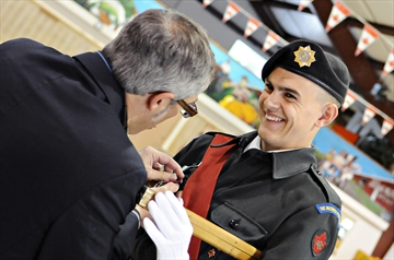 Warrant Officer Logan Pepper can barely contain his excitement as Parry Sound - Muskoka MP Tony Clement pins the Lord Strathcona Medal to his chest during the Muskoka Pioneers' annual parade on Saturday, June 2. (Photo by Louis Tam)