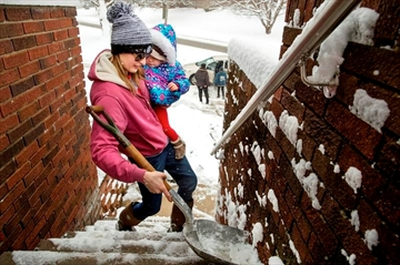 Morgan Miller carries her one-year-old daughter Mia Jennings in one arm as she shovels the stairs to her Springfield home with the other Sunday, Jan. 13, 2019. Miller said she's learned how to do a lot of things while holding a baby in the last year. (Ted Schurter/The State Journal-Register via AP)