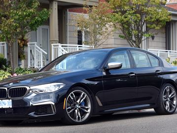 The fastest 5 Series model ever, the 2018 BMW M550i sport sedan is shown in Carbon Black Metallic.