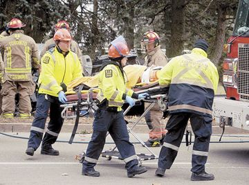 Toronto paramedics transport one of the victims of a two-vehicle crash on Danforth Avenue east of Birchmount Road on Wednesday. The driver had to be extricated from the vehicle.