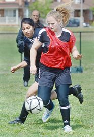 Stouffville Spartans Rebecca Deforest (front) tries to keep the ball away from a close-checking Sama Moosa of St. Robert CHS of Thornhill, during senior girl's action Friday in Stouffville.