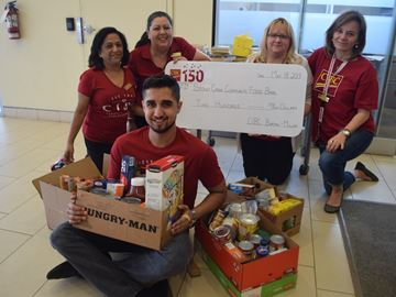 CIBC 393 Barton St. E. branch employees Gary Tiwana, Sunita Maheshwari, Angie MacKenzie, Elizabeth Gabriel and Liz Maslen, front to back, left to right, display a $200 cheque and five boxes of food donations for the Stoney Creek Community Food Bank. The branch collected the money through a used book drive and gathered up the non-perishable food items via casual dress days.