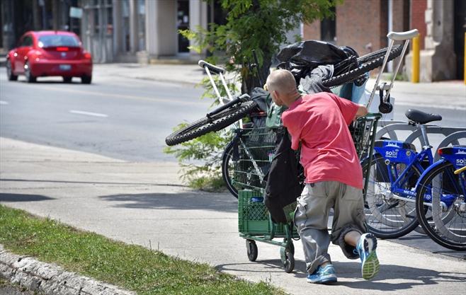Matthew Edgeworth pushes his cart of belongings and scrap metal up John Street.