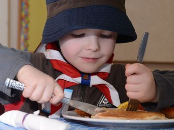 Beaver Liam Campbellford, 5, digs in during the 20th Burlington Scout pancake breakfast at Burlington East Presbyterian Church on Saturday morning. This celebration of Scouting Founder Lord Baden Powell's birthday also kicked off the Scout Group's Maple Syrup sales efforts.