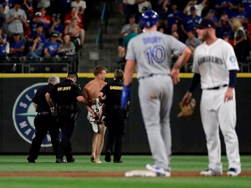 Toronto Blue Jays' Brandon Drury (10) stands on second base as a man who jumped out of the stands and ran naked in the Safeco Field outfield is taken away by sheriff's deputies during the ninth inning of the Blue Jays' baseball game against the Seattle Mariners, Saturday, Aug. 4, 2018, in Seattle. U.S. authorities say a Vancouver resident who ran naked onto a baseball field during a game in Seattle is set to appear in court today to face a criminal trespassing charge. THE CANADIAN PRESS/AP/Ted S. Warren