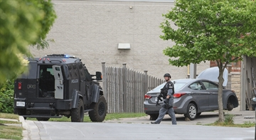 Members of the Hamilton Police Service's Emergency Response Unit leave a home on Candlewood Drive Thursday after executing a search warrant looking for at least four long guns stolen during a break in Tuesday night.