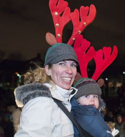 Natalie Poissant and her son Conor, 10 months, pick up a raffle prize during the Christmas in the Park holiday tree lighting event in Kew Gardens Dec. 7.