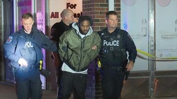 Hamilton police escort a man from a building at Newlands Avenue and Kenilworth Avenue North in Hamilton.