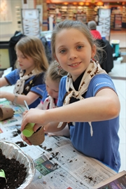 local members of Girl Guides Canada recognized Earth Day April 18 at Eastgate Square by participating in a variety of activities. Show here, Ella Hume plants Kale seeds.