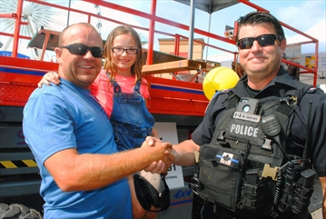 Sgt. Marc Garrels, preparing to go into his cage on Clifton Hill, thanks Wasaga Beach resident Doug Macham, with daughter Serena, for donating to the jar calling for Garrels to be freed.